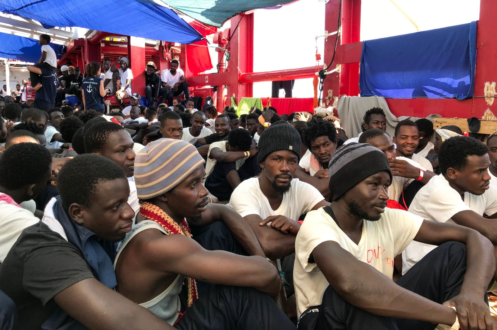Rescued migrants gather aboard the 'Ocean Viking' rescue ship, jointly operated by French NGOs SOS Mediterranee and Medecins sans Frontieres (MSF Doctors without Borders) on August 23, 2019, (AFP Photo)
