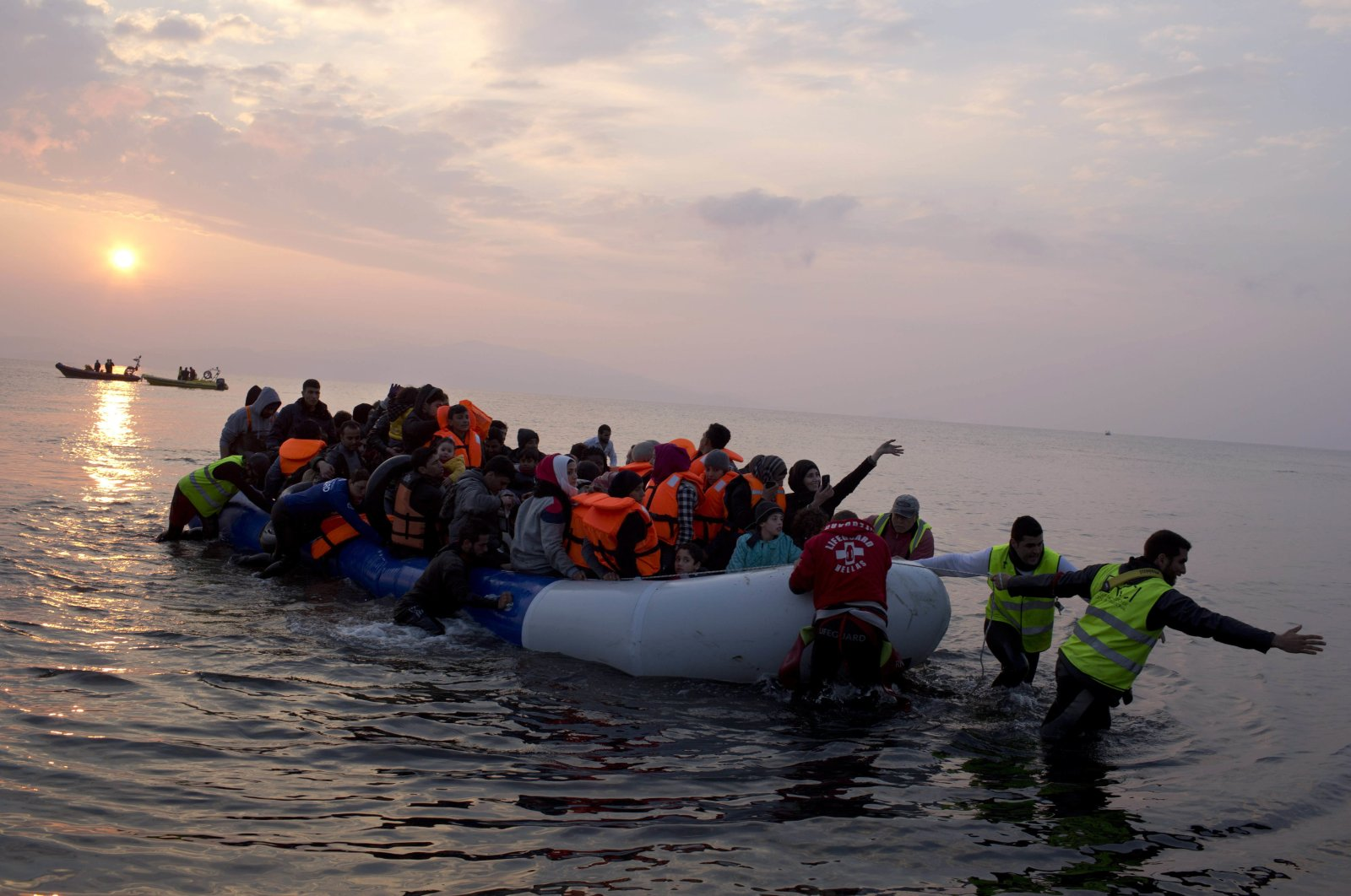 Volunteers help migrants and refugees on a dingy as they arrive at the shore of the northeastern Greek island of Lesbos, after crossing the Aegean sea from Turkey, March 20, 2016. (AP Photo)