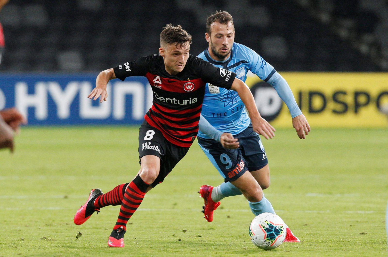 Sydney FC's Adam Le Fondre challenges Wanderers' Jordan O'Doherty during an A-League match in Sydney, Saturday, March 21, 2020. (AFP Photo)