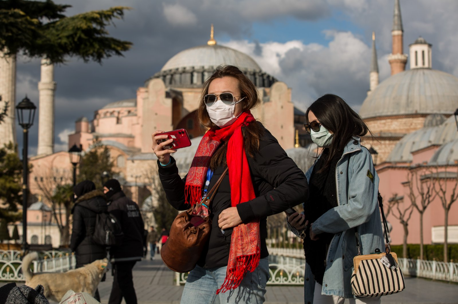 Tourists wearing protective face masks due to coronavirus concerns stroll in Sultanahmet Square in Istanbul, Turkey, Wednesday, March 18, 2020. The Byzantine-era monument of Hagia Sophia is seen in the background. (DHA Photo)