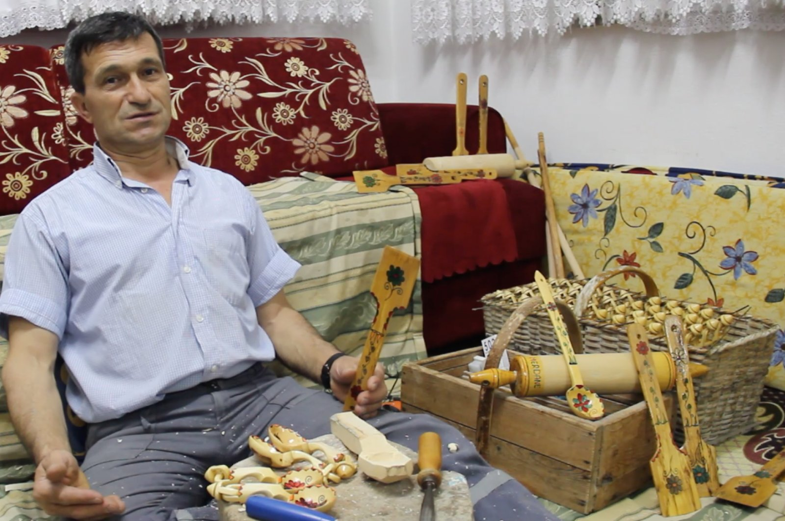 Lütfü Uğur poses with his wooden spoons, tablespoons, ladles and other products. (AA Photo)