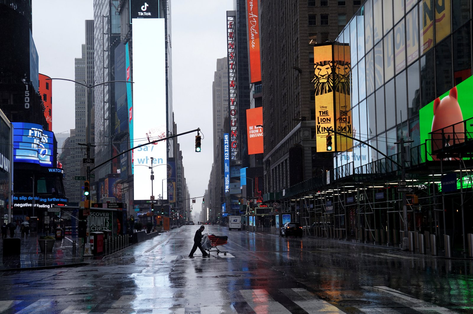 A homeless person pushes his belongings through a deserted Times Square, New York, Monday, March 23, 2020. (Reuters Photo)