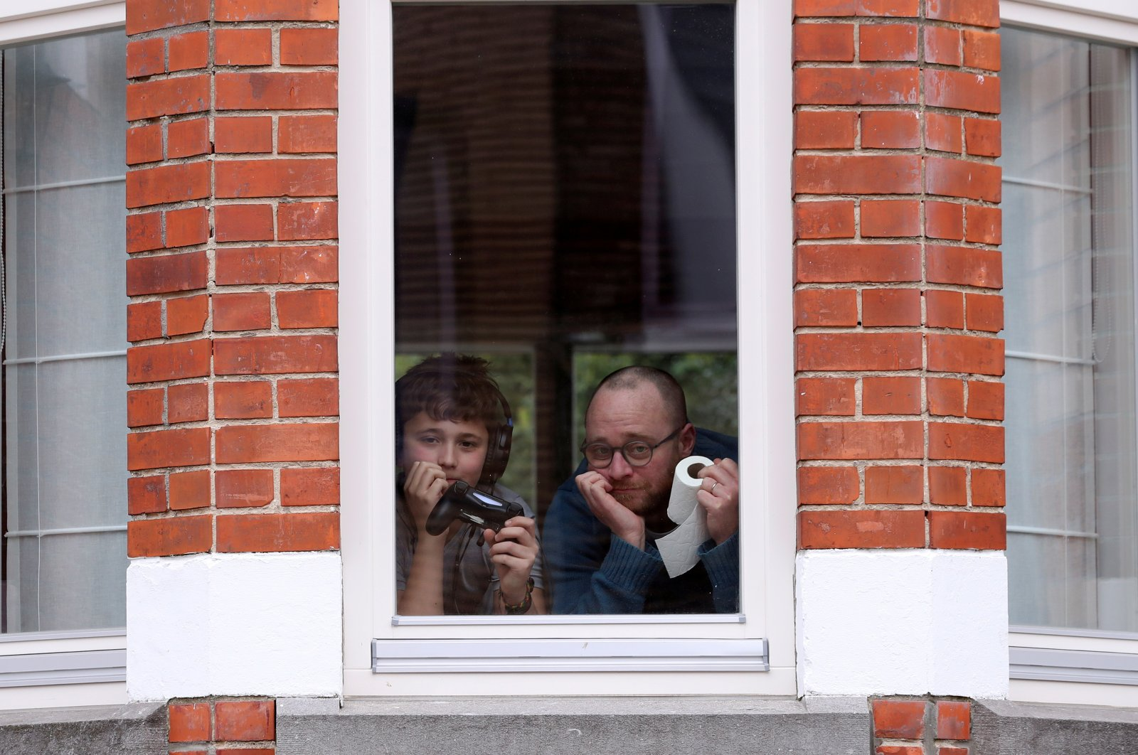 Resident Laurent Lanthier and his son Robin pose behind the window of their home during a coronavirus lockdown imposed by the Belgian government in an attempt to slow down the coronavirus outbreak, in Brussels, Belgium, March 19, 2020. (Reuters Photo)