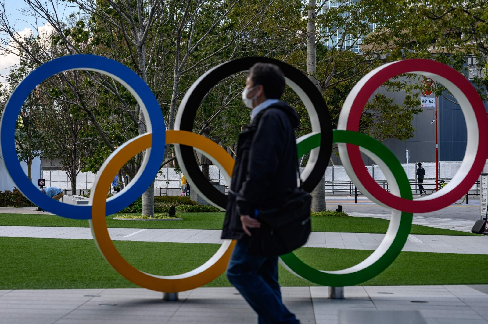 A man wearing a face mask walks in front of the Olympic Rings in Tokyo, Japan, Wednesday, March 11, 2020. (AFP Photo)
