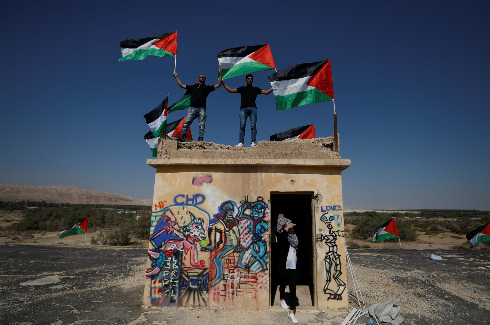 Demonstrators hold Palestinian flags during a protest against illegal settlements near the Dead Sea in the Israeli-occupied West Bank, Sept. 28, 2019. (Reuters Photo)