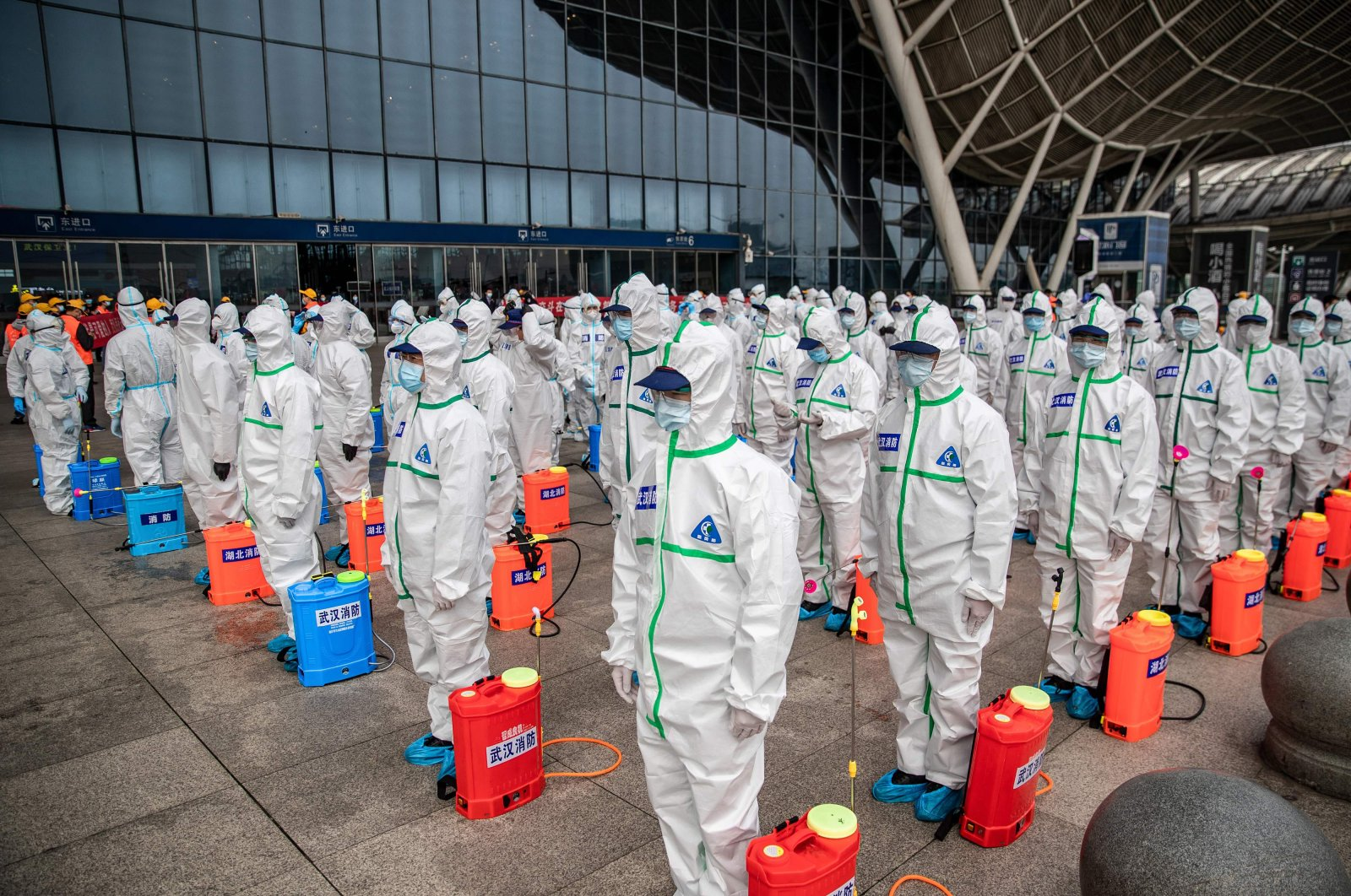 Staff members line up at attention as they prepare to spray disinfectant at Wuhan Railway Station, Wuhan, March 24, 2020. (AFP Photo)