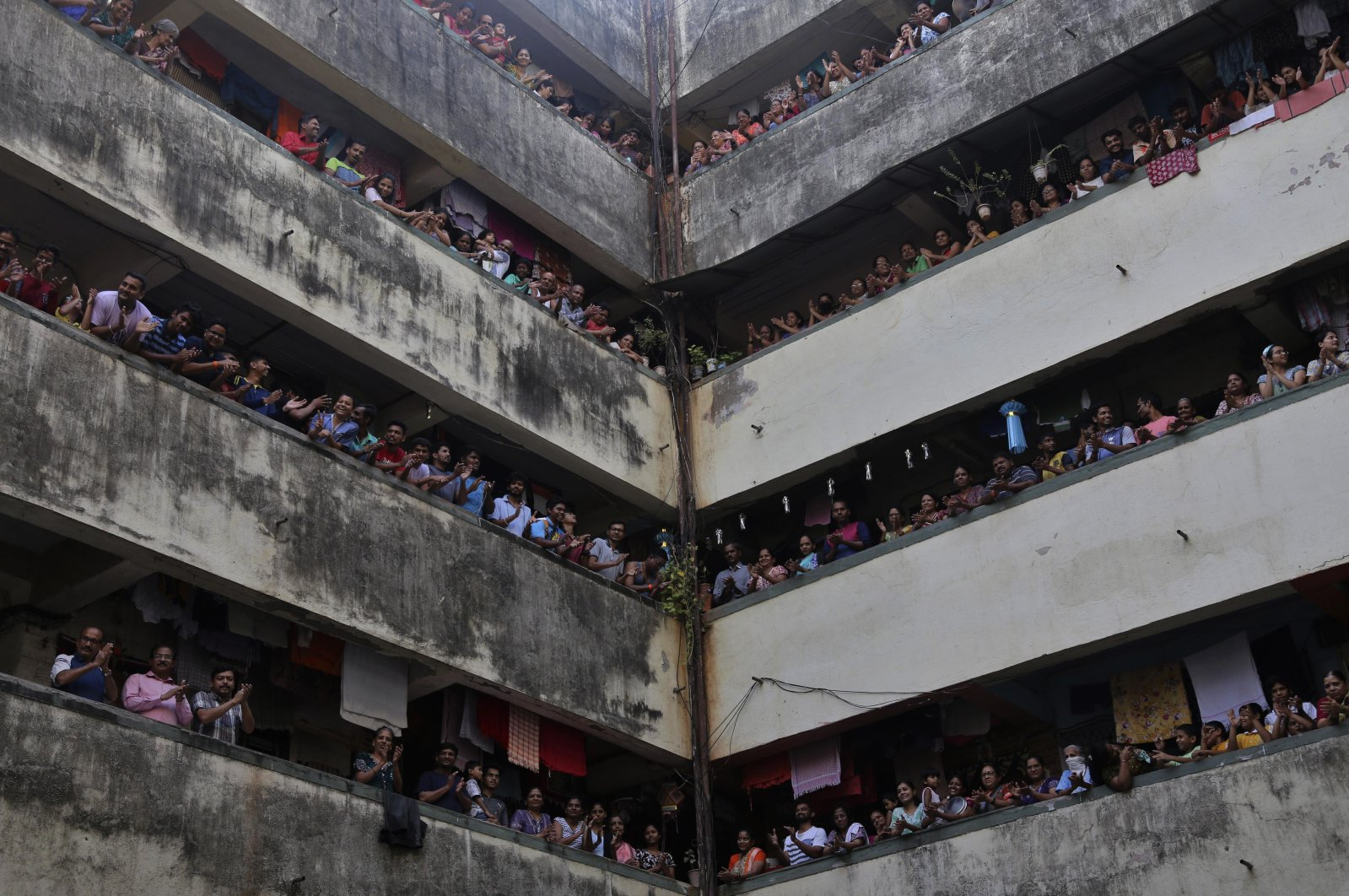 People clap from balconies in a show of appreciation for health care workers at a chawl, Mumbai, India, Sunday, March 22, 2020. (AP Photo)