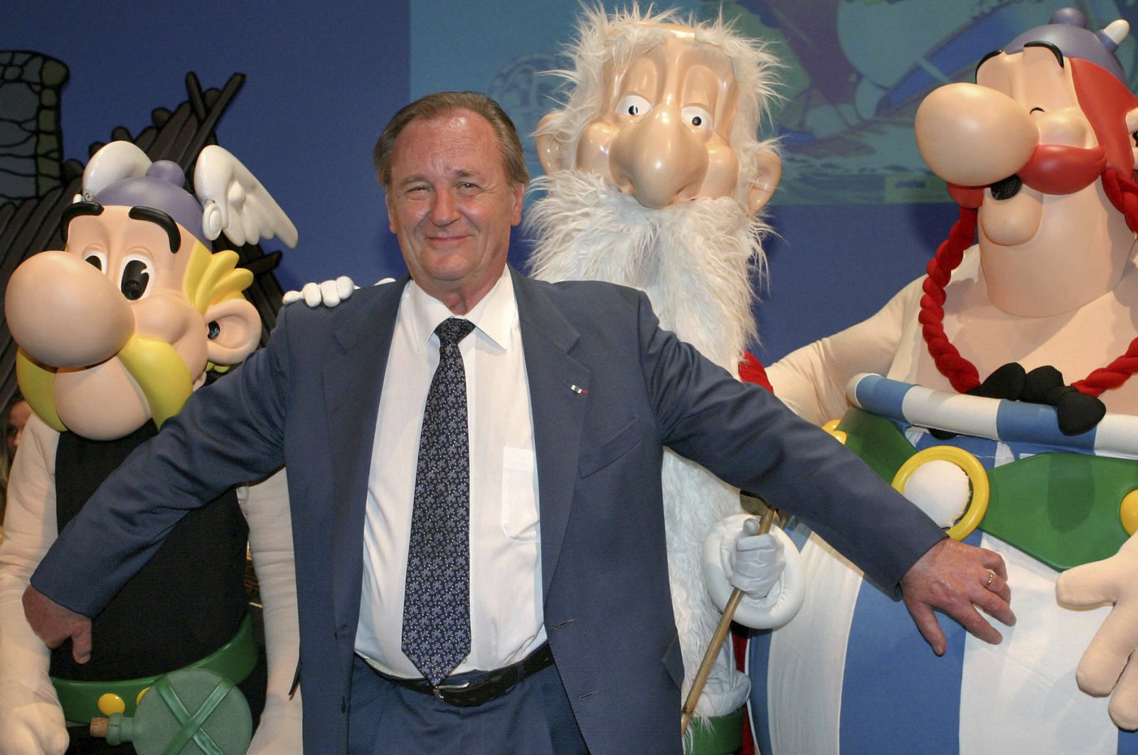 """In this June 12, 2004 file photo, French illustrator Albert Uderzo poses with characters of his famous comics, Asterix, left, druid Miraculix, behind, and Obelix , right, during the awarding of the so-called """"Max & Moritz"""" award by the Erlangen Comic Salon2004 in Erlangen, southern Germany. (AP Photo)"""