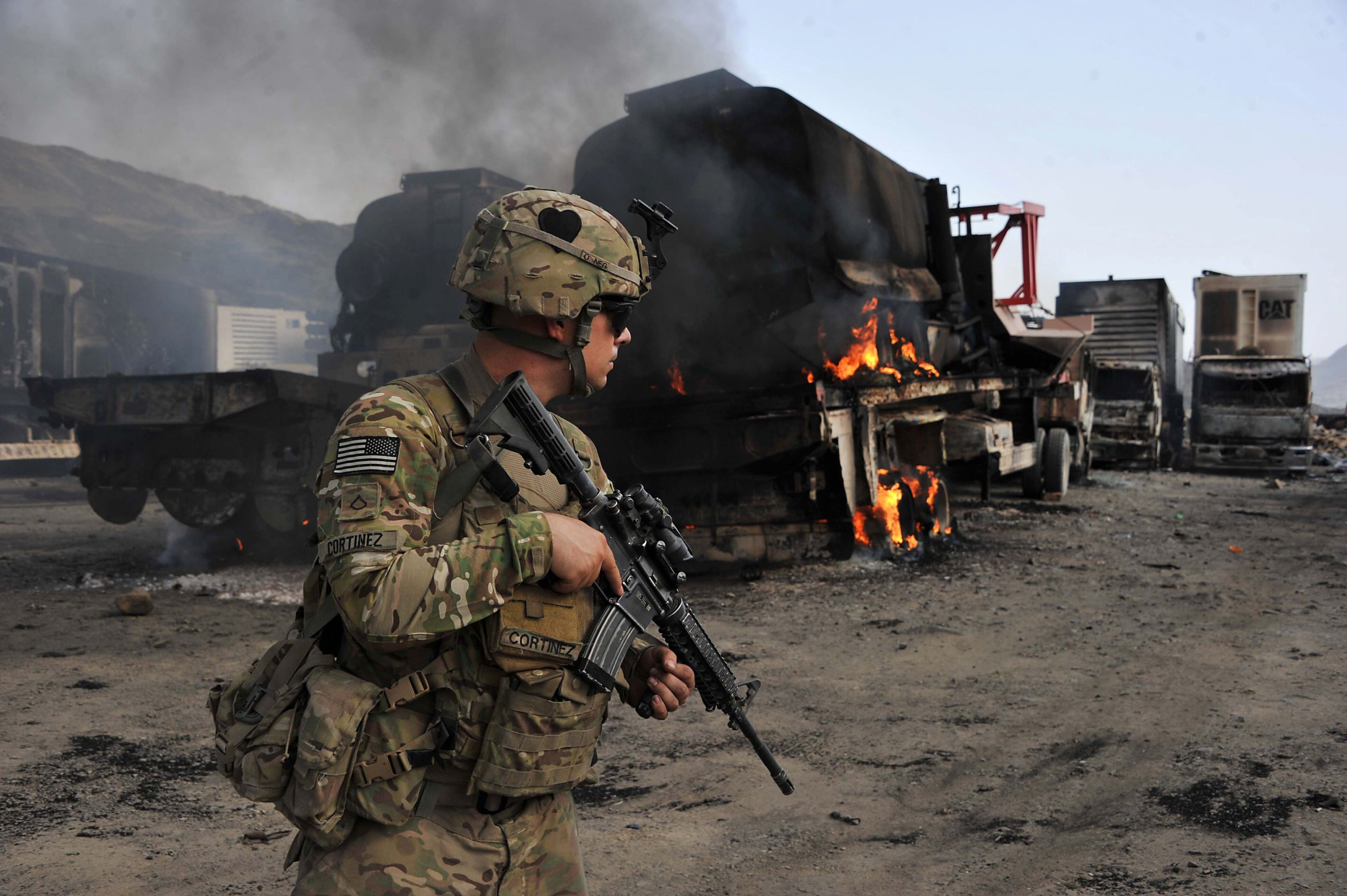 A US soldier investigates the scene of a suicide attack at the Afghan-Pakistan border crossing in Torkham, Nangarhar province, June 19, 2014. (AFP)