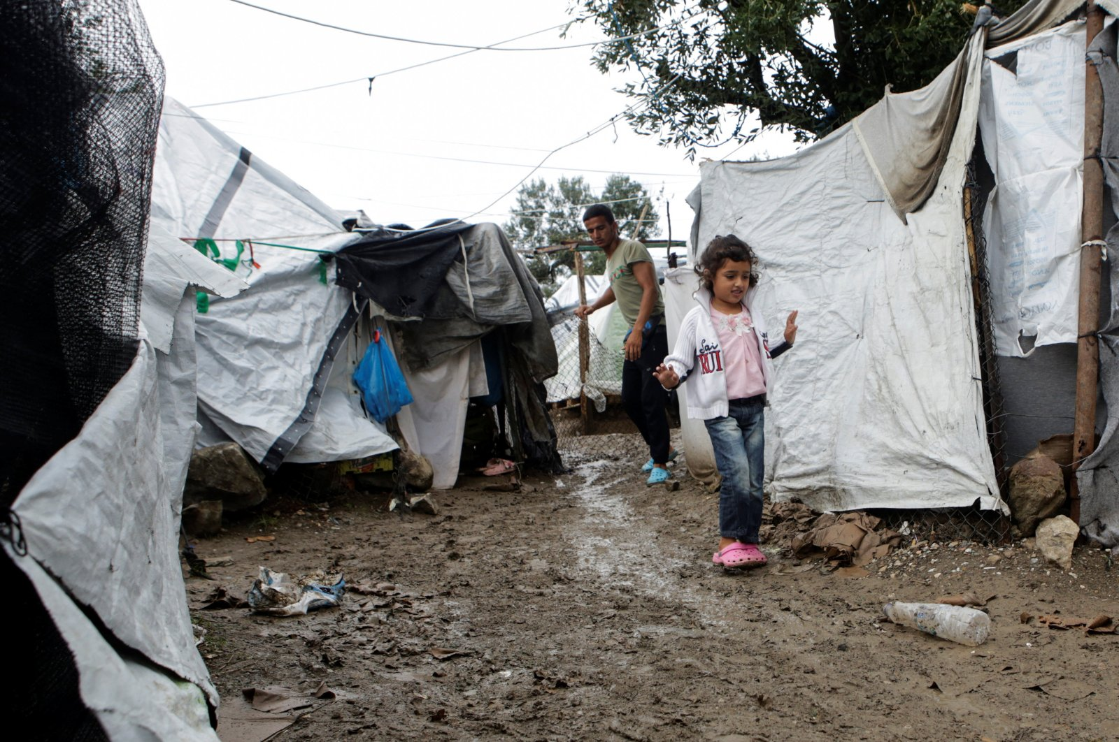 A girl makes her way next to tents at a makeshift camp for refugees and migrants next to the Moria camp, following a rainfall on the island of Lesbos, Greece, October 8, 2019. (REUTERS Photo)