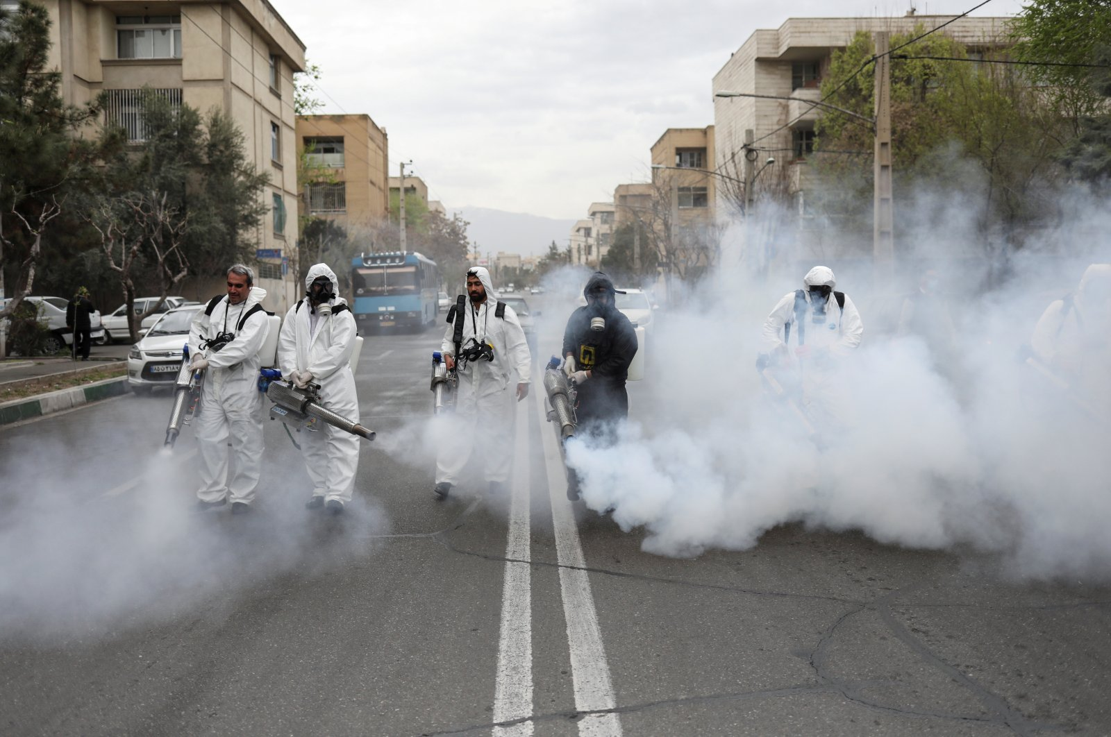 Members of firefighters wear protective face masks as they disinfect the streets, Tehran, March 18, 2020. (REUTERS Photo)