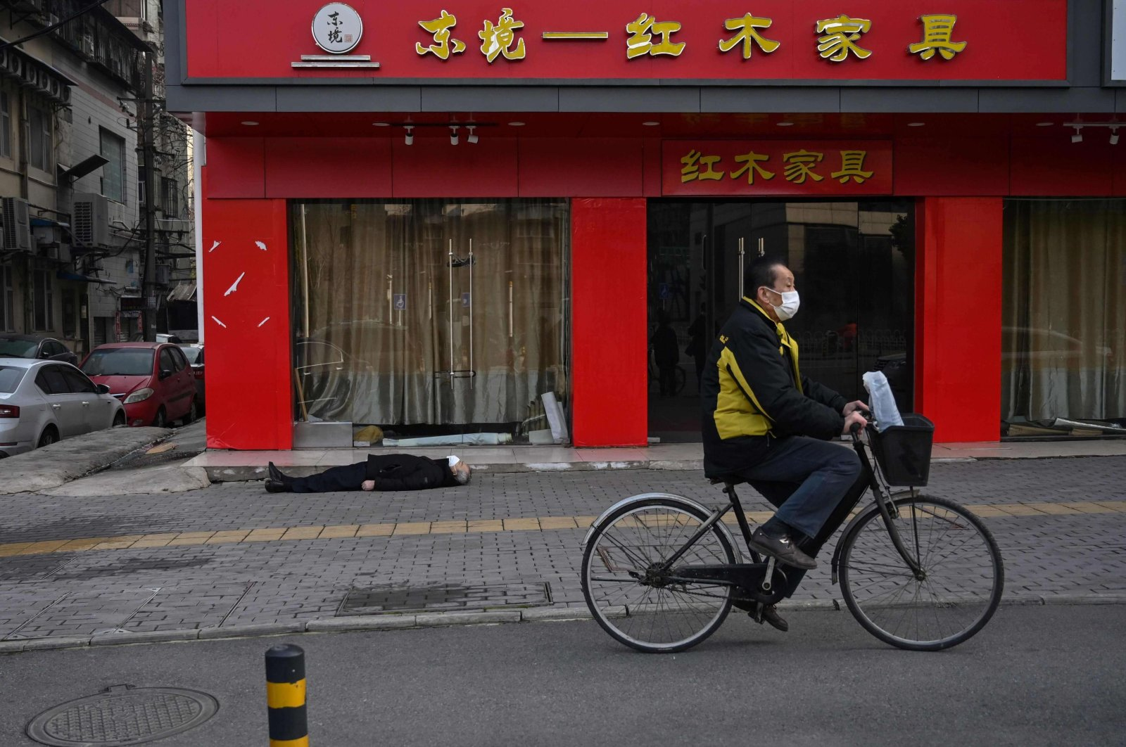 An elderly man wearing a face mask who collapsed and died lays on a street near a hospital as another man rides a bicycle past him in Wuhan, China, Jan. 30, 2020. (AFP Photo)