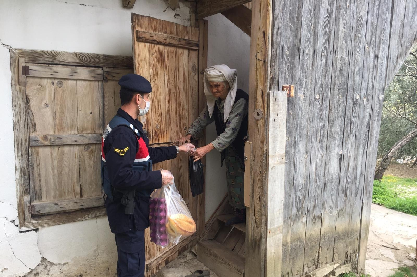 A gendarme officer delivers groceries he bought for an elderly woman, Muğla, Wednesday, March 25, 2020. (AA Photo)