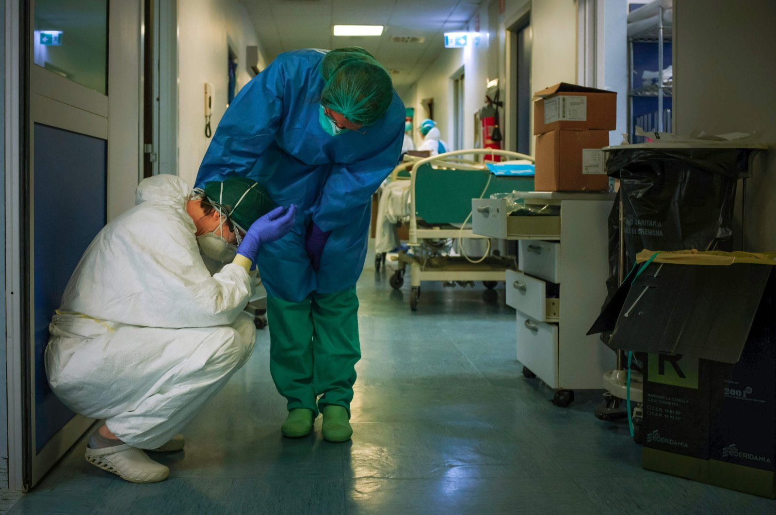 A nurse wearing a protective mask and gear comforts another at the Cremona hospital, southeast of Milan, Lombardy, March 13, 2020. (AFP Photo)