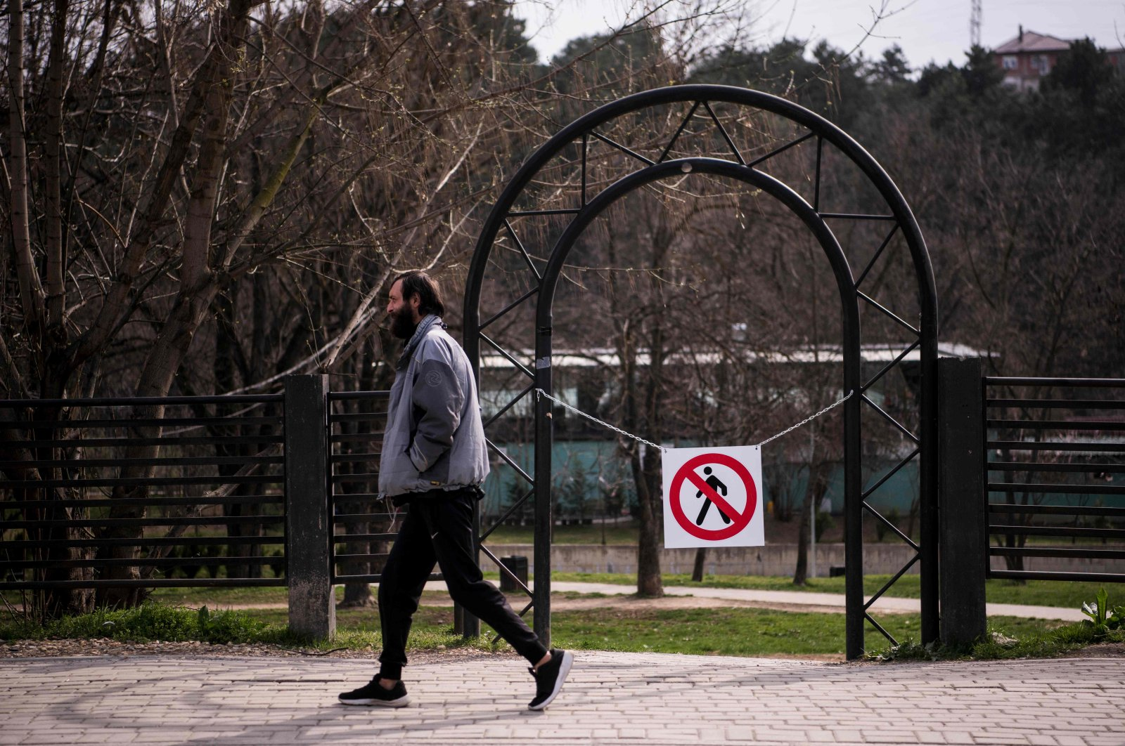 A man walks past a no-entry sign across a gate into a park, Pristina, March 22, 2020. (AFP Photo)