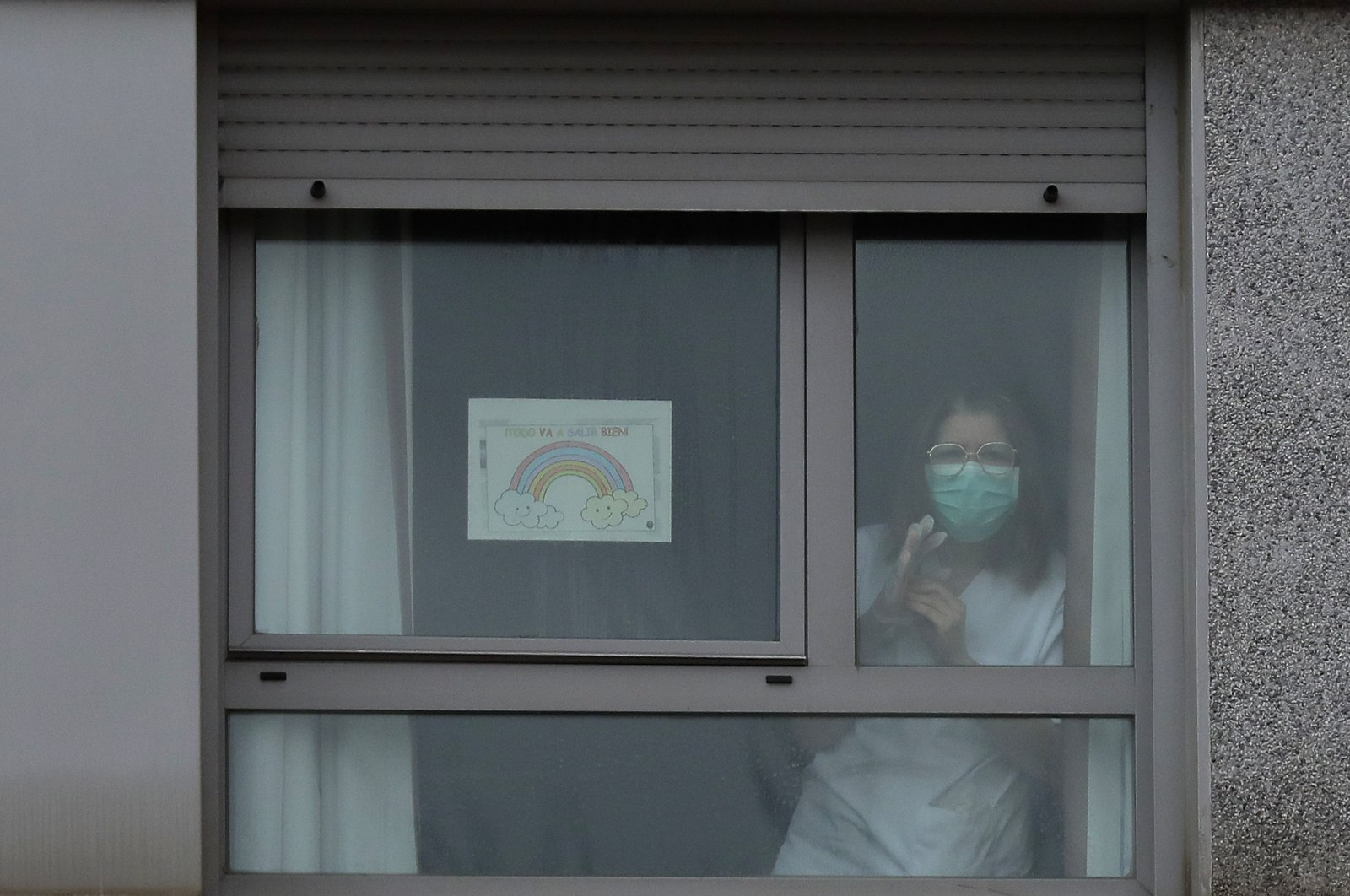 """A nurse looks out from a window next to a banner reading in Spanish """"Everything is going to be all right"""" inside of a nursing homes, Madrid, Tuesday, March 24, 2020. (AP Photo)"""