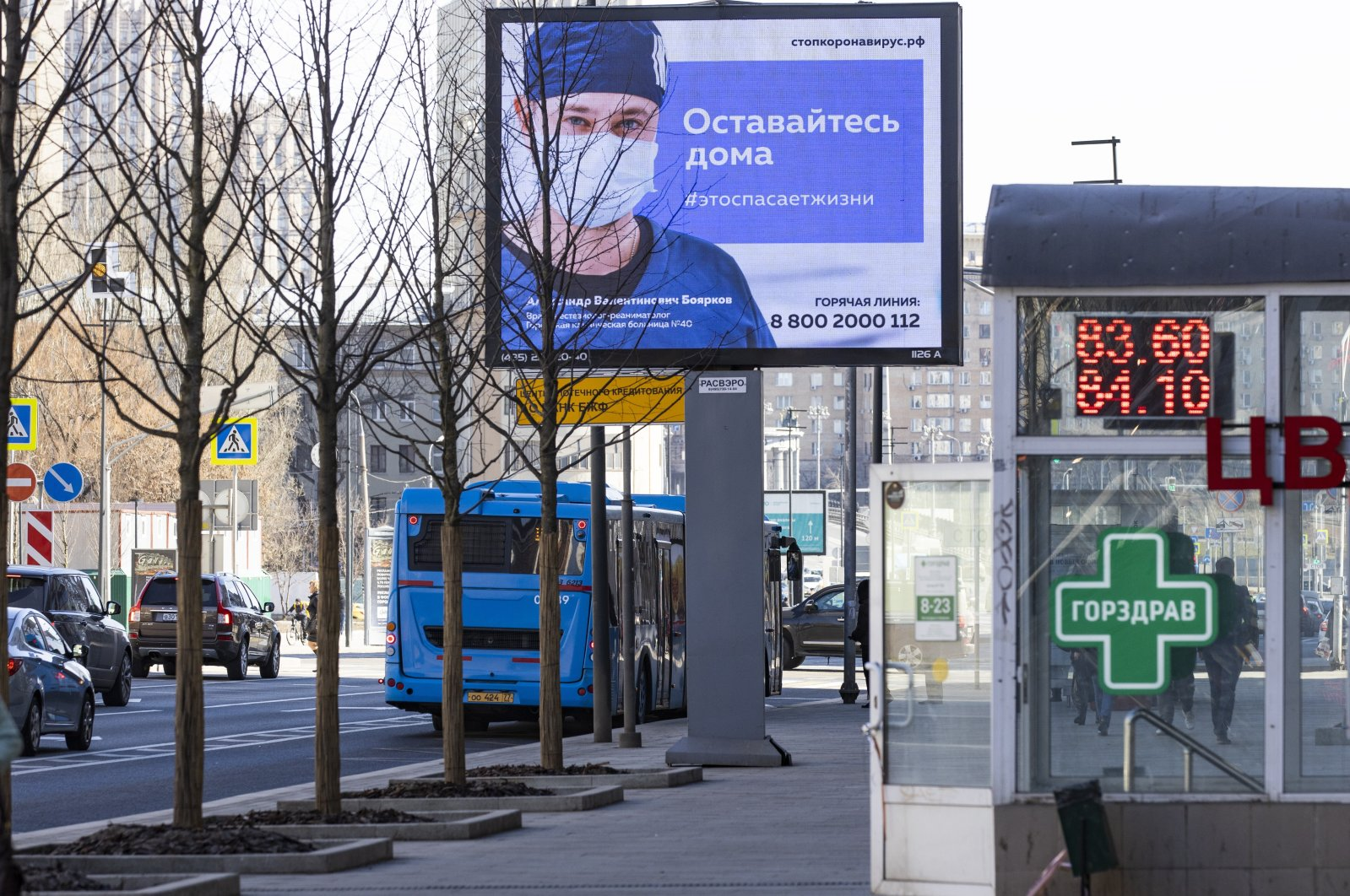"""An electronic billboard showing a doctor wearing a medical mask with the words reading """"Stay home, it will save a life"""" in a street in Moscow, Russia, Wednesday, March 25, 2020. (AP Photo)"""