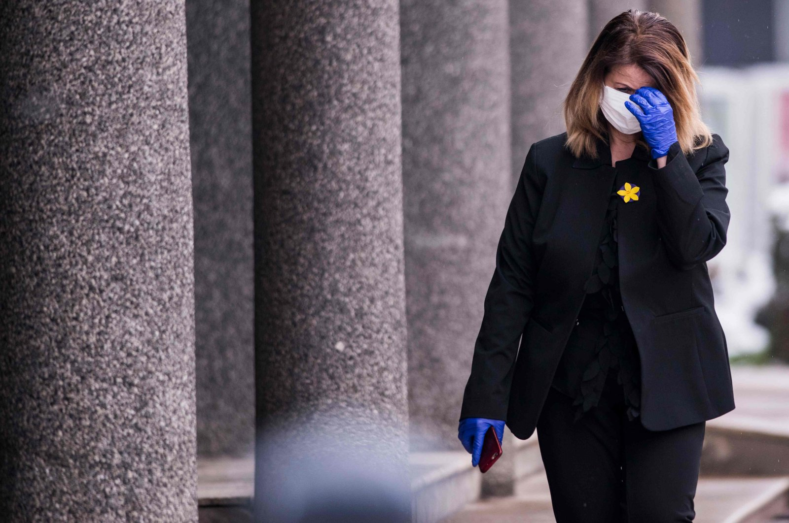 A lawmaker wearing protective mask and gloves arrives for an extraordinary session at the Kosovo Parliament in Pristina on March 25, 2020 (AFP Photo)