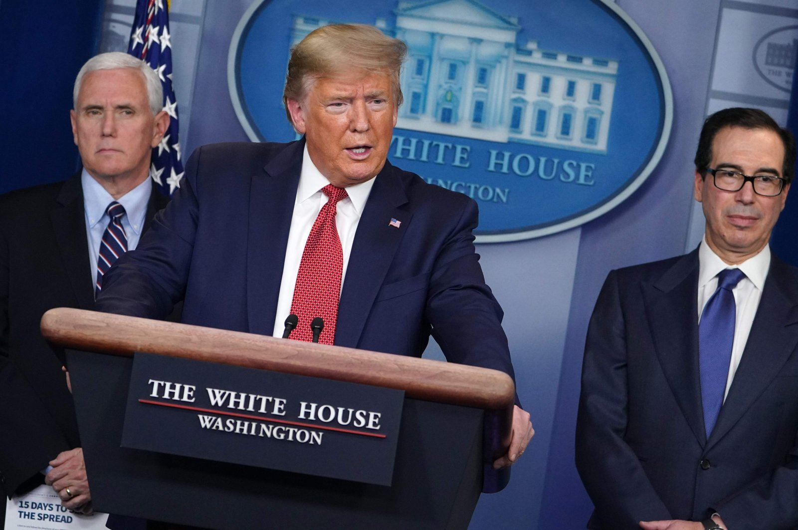 US President Donald Trump, flanked by US Secretary of the Treasury Steven Mnuchin (R) and US Vice President Mike Pence, speaks during the daily briefing on the novel coronavirus, COVID-19, in the Brady Briefing Room at the White House on March 25, 2020, in Washington, DC. (AFP Photo)