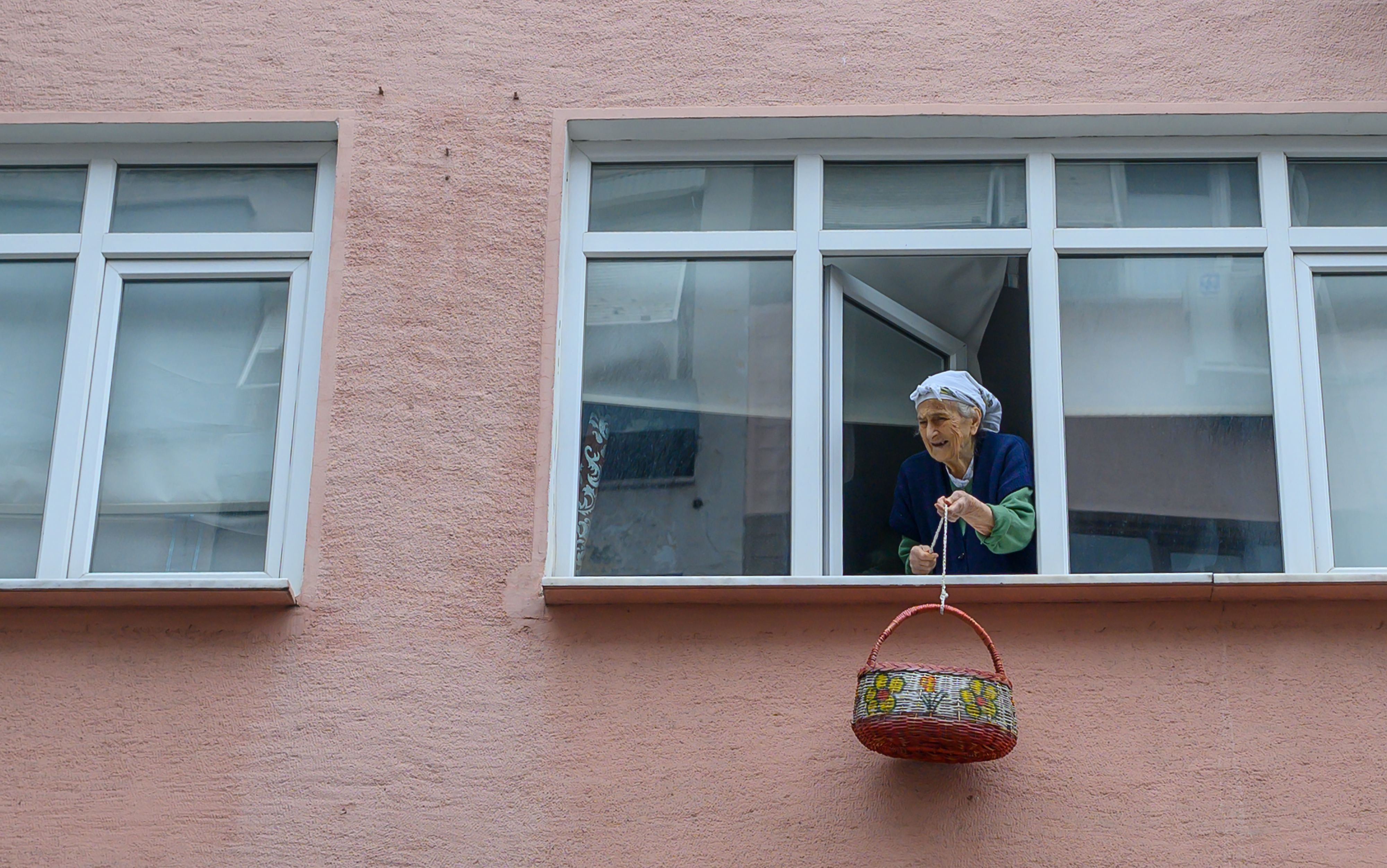 Sevim Özkan, an 85-year-old Turkish woman, waits with her basket for her neighbor (not pictured) to bring her medicine in Kadıköy, Istanbul, Monday, March 23, 2020. (AFP Photo)