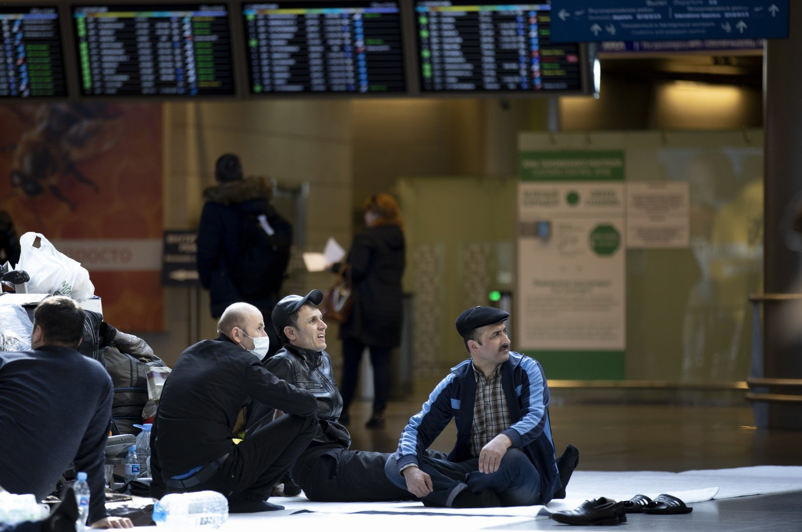 Tajikistani nationals sit on the floor waiting for a plane to return to their home country at the Vnukovo International Airport, 35 km southwest of Moscow, Russia, Tuesday, March 24, 2020. (AP Photo)