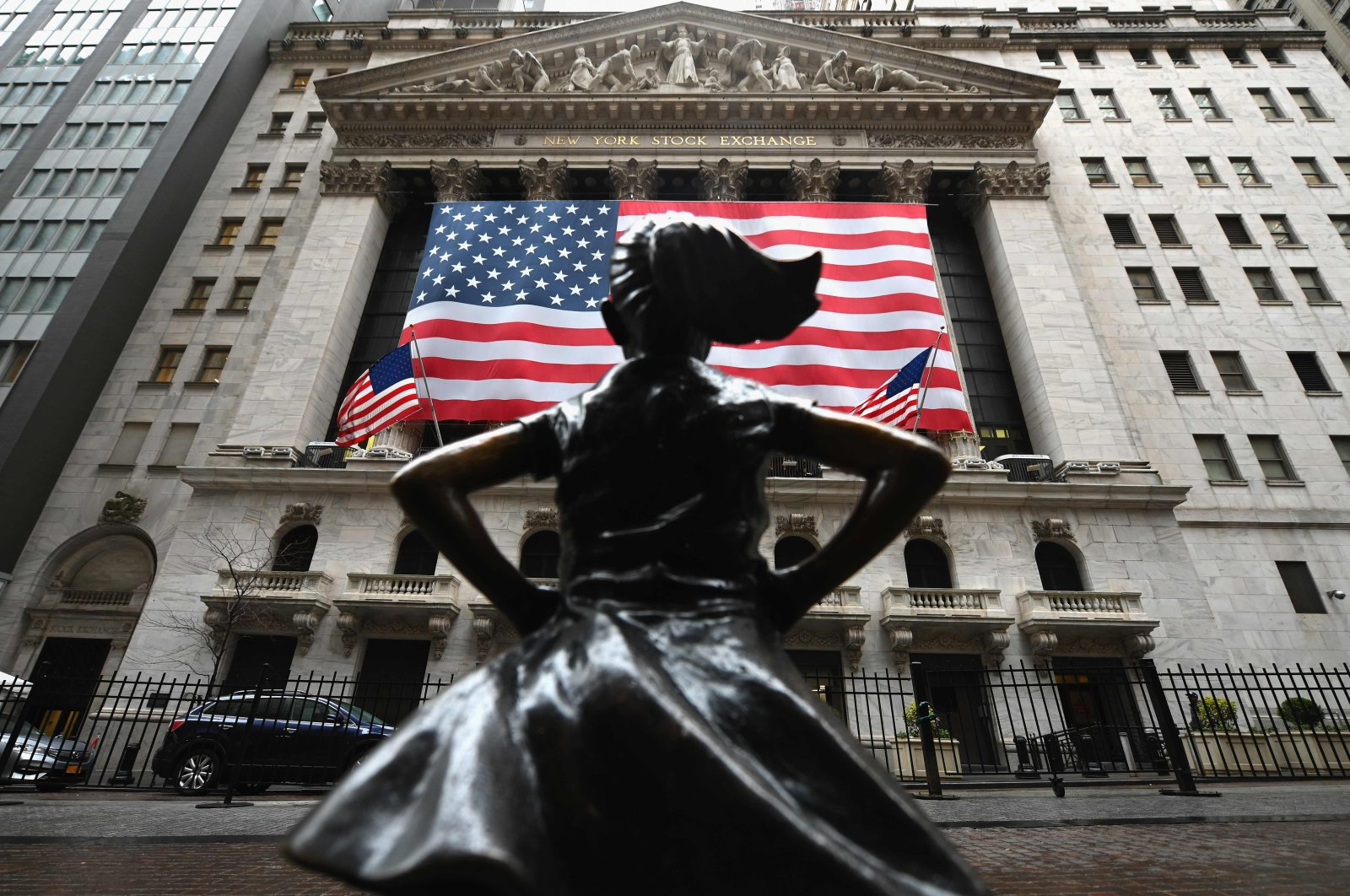 """""""The Fearless Girl"""" statue stands in front of the New York Stock Exchange near Wall Street on Monday, March 23, 2020, New York City, New York. (AFP Photo)"""
