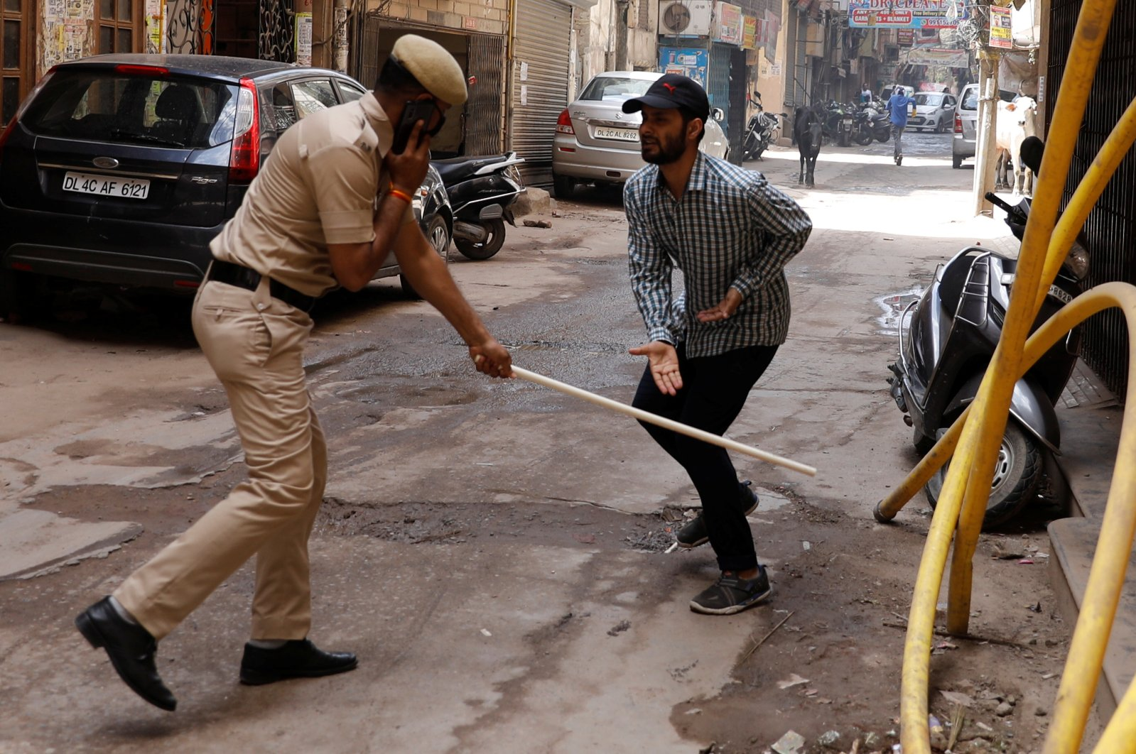 A police officer wields his baton against a man as a punishment for breaking the lockdown rules, New Delhi, Wednesday, March 25, 2020. (Reuters Photo)