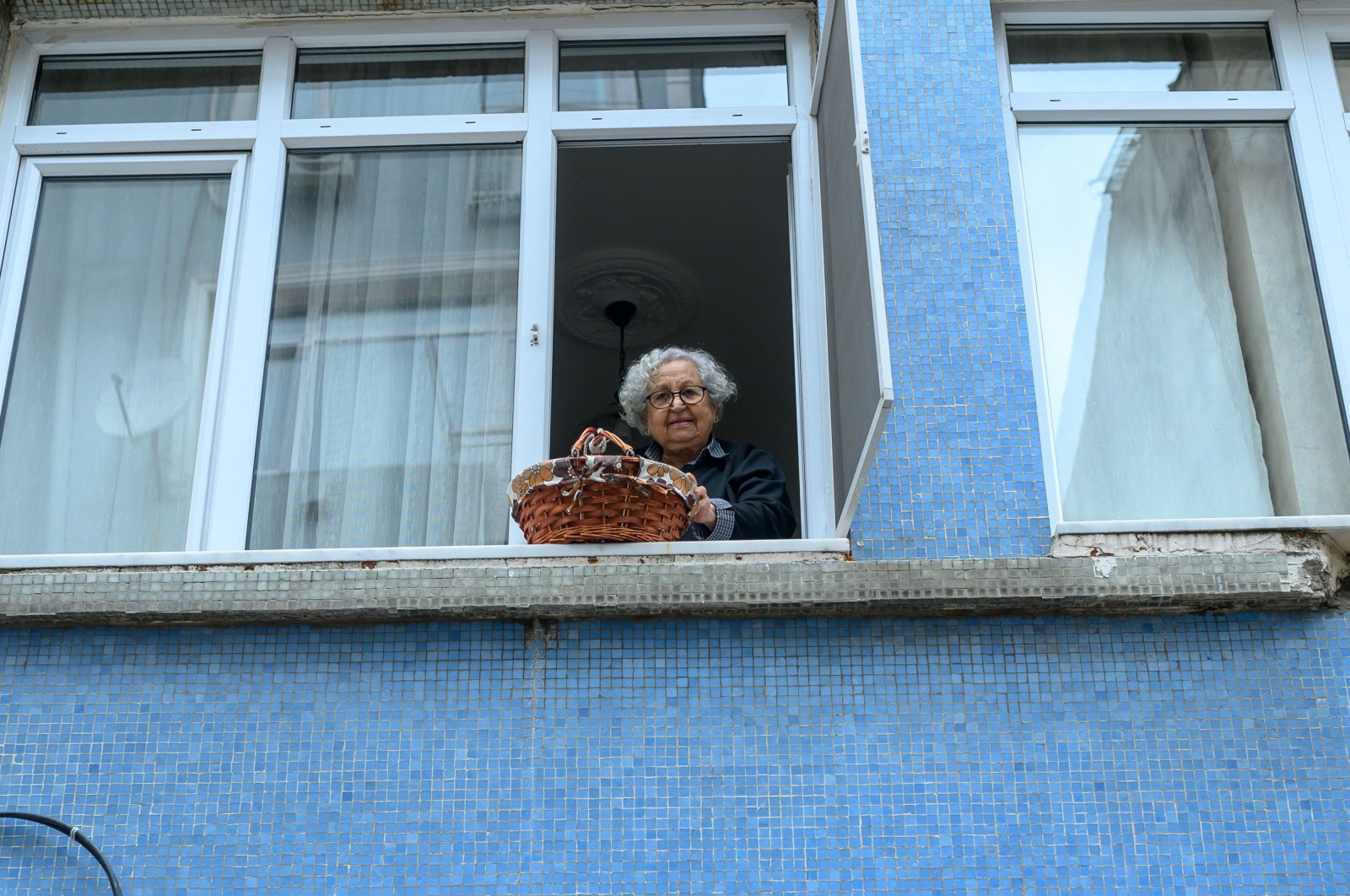 Lütfiye Yeşilbaş, an 89-year-old Turkish woman who lives alone in her home, lowers her basket in Kadıköy, Istanbul, Monday, March 23, 2020. (AFP Photo)