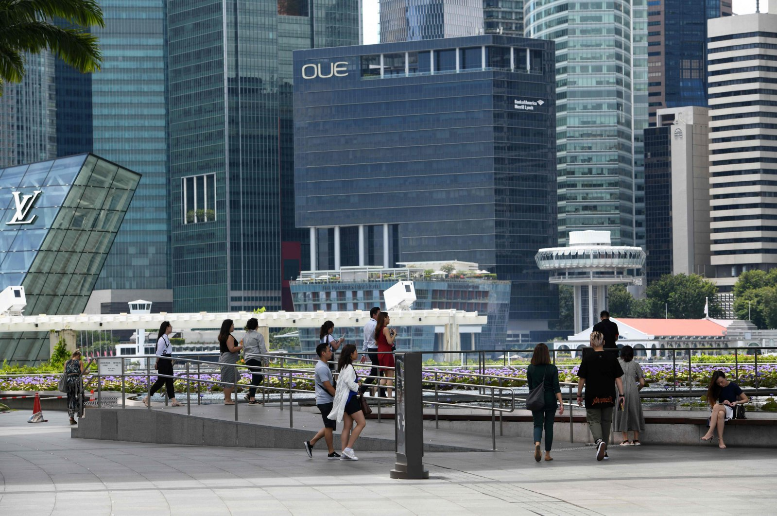 People walk near commercial buildings in the central business district in Singapore, Feb. 18, 2020. (AFP Photo)