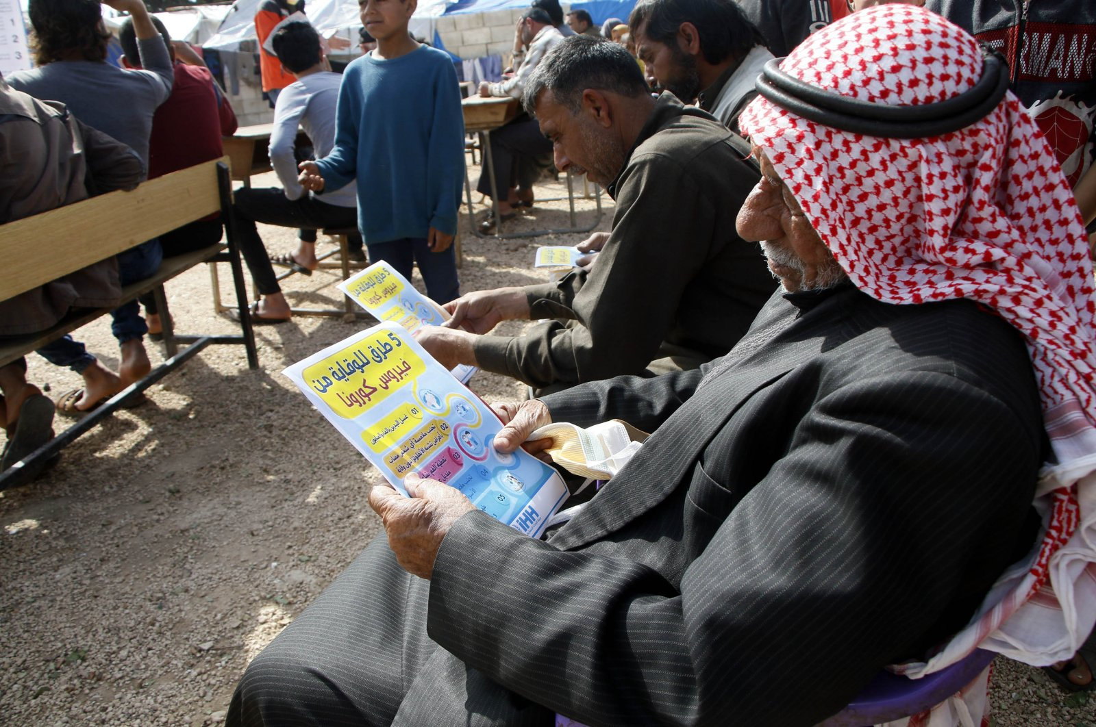 The Humanitarian Relief Foundation (İHH), is working to inform the displaced Syrians in Idlib about the coronavirus by hanging banners and handing out brochures, and conducting seminars, Thursday, March 26, 2020. (DHA)
