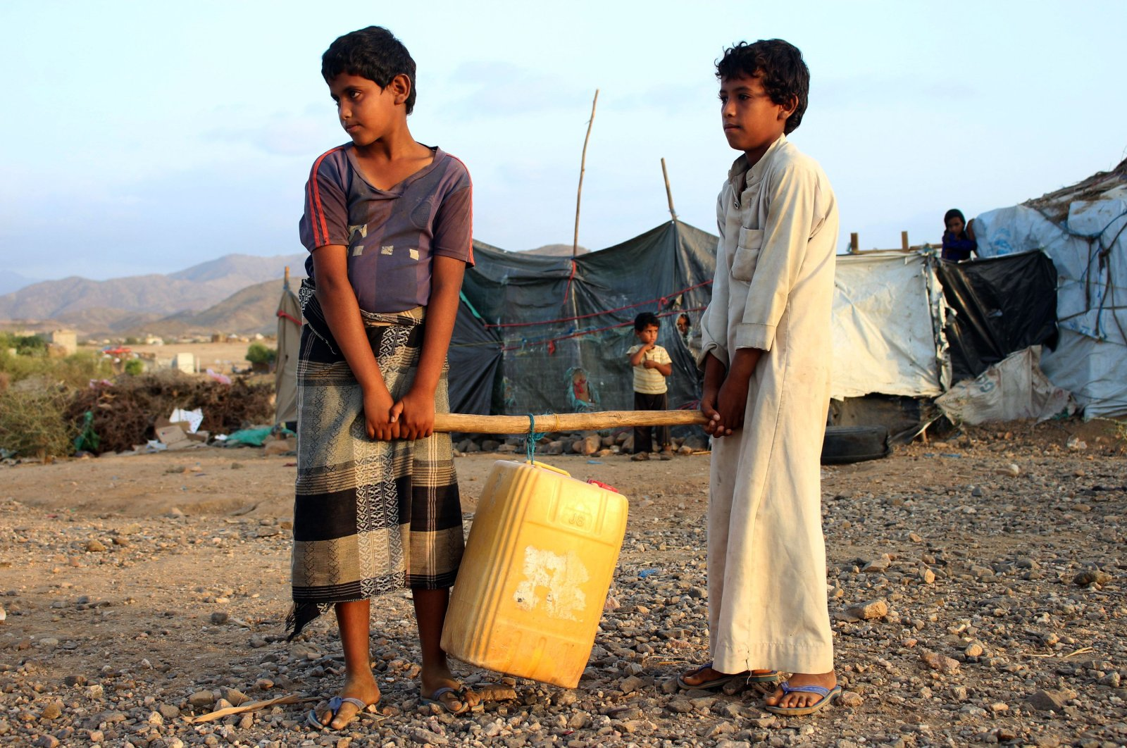 Boys carry a jerrycan filled with water from a cistern at a makeshift camp for displaced Yemenis in severe shortage of water in the northern Hajjah province, Tuesday, March 24, 2020. (AFP Photo)