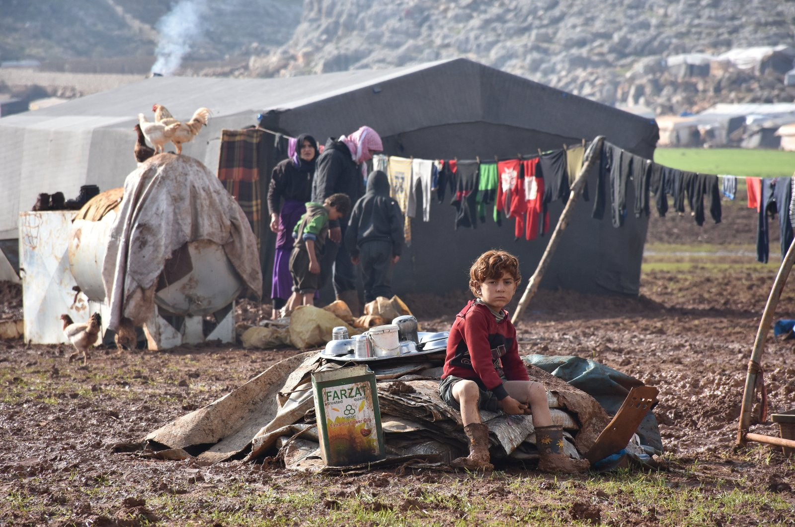 Civilians who fled the Assad regime in Idlib try to survive amid mud and cold living in tents in areas near the Turkish border, Jan. 5, 2020. (AA Photo)