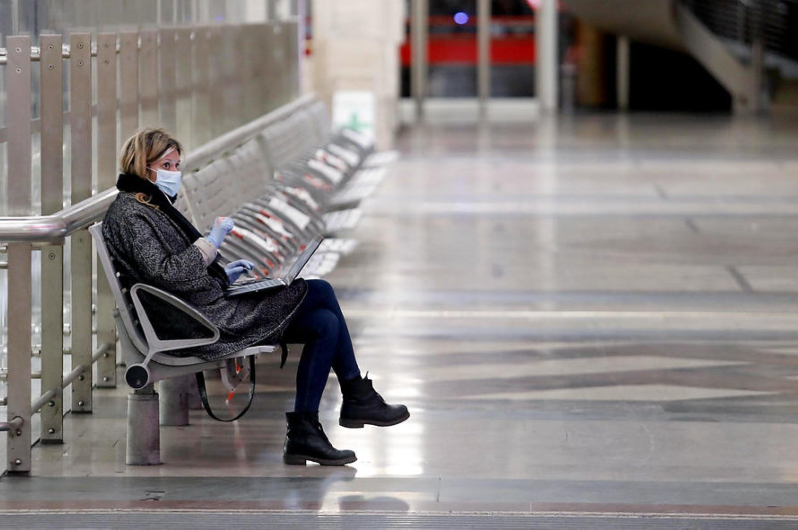 A woman wearing a face protective masks sits at Milan Central Station, Milan, Italy, Wednesday, March 25, 2020. (EPA Photo)