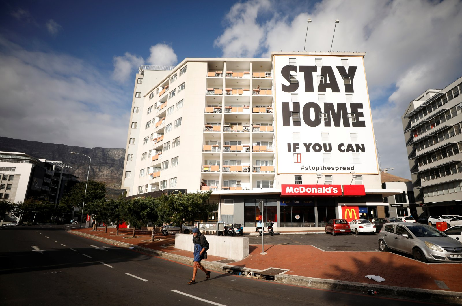 A man walks past a poster covering the side of a building ahead of a 21-day lockdown, Cape Town, Thursday, March 26, 2020. (REUTERS Photo)