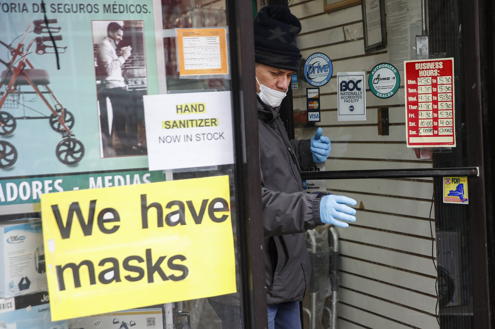 A customer leaves a shop advertising personal protective equipment near Elmhurst Hospital Center, New York, Wednesday, March 25, 2020. (AP Photo)