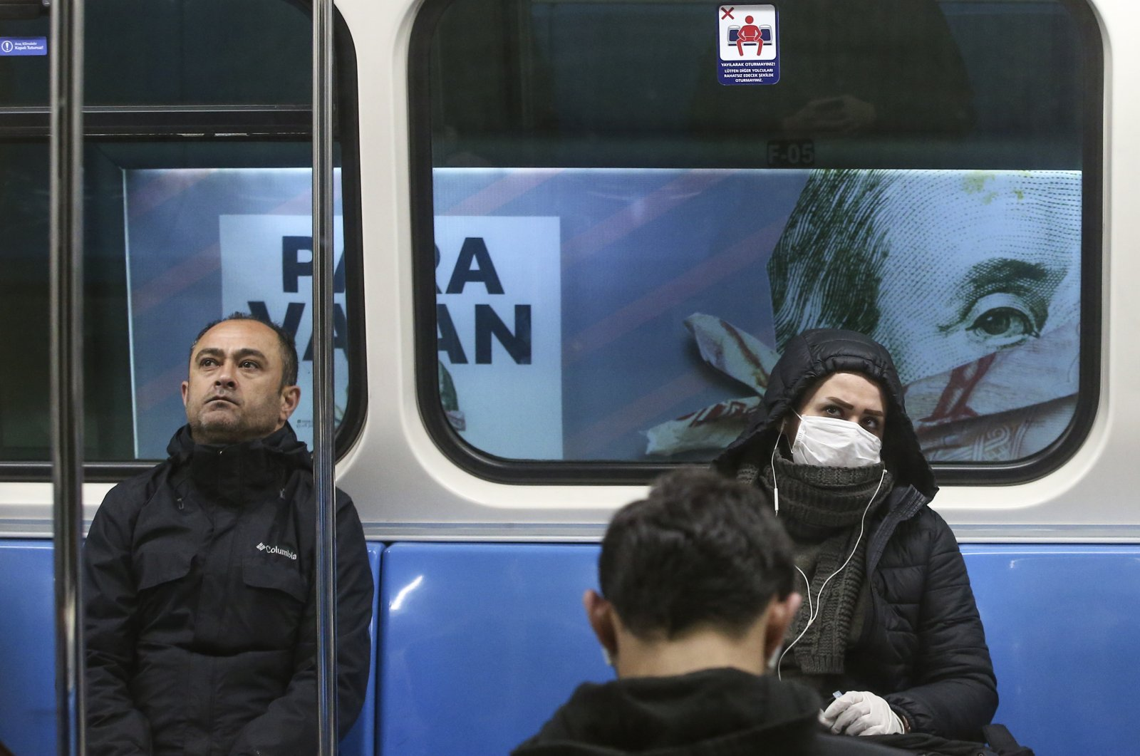 Commuters in an underground train, some wearing masks, are driven past a billboard of a book advertisement featuring a picture of U.S. President Benjamin Franklin on the $100 bill, in Istanbul, Turkey, Wednesday, March 25, 2020. (AP Photo)
