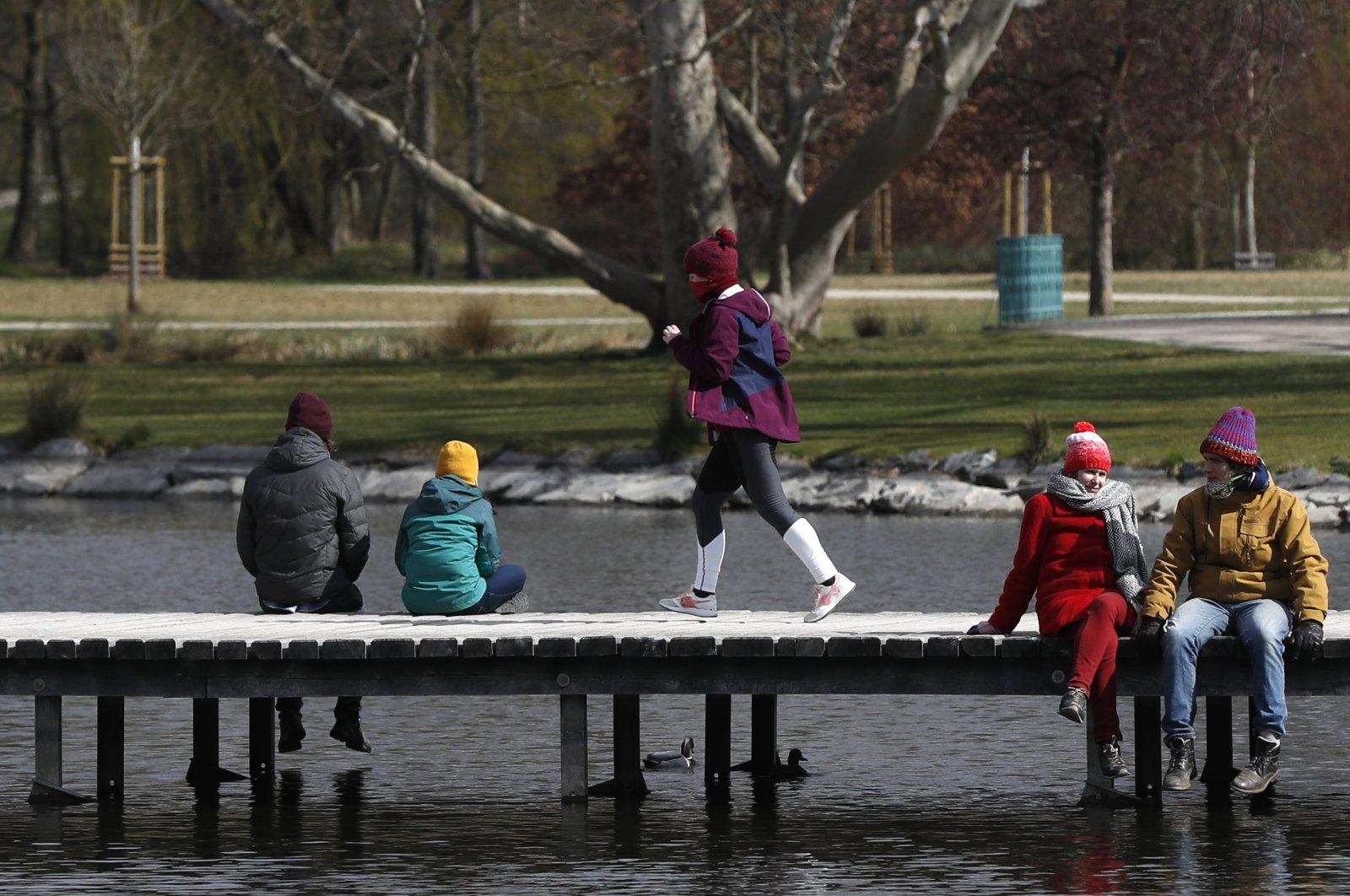 A young woman wearing a face mask runs across a wooden bridge in a park, Prague, Czechia, March 22, 2020. (AP Photo)