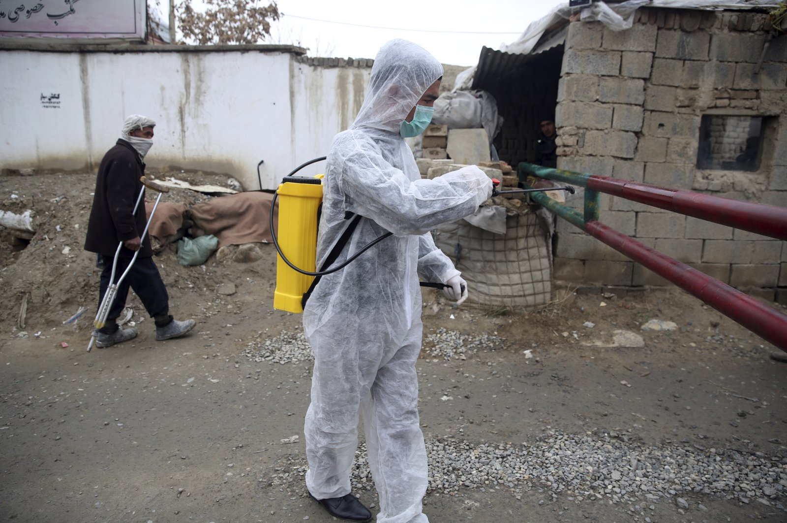 A volunteer in a protective suit sprays disinfectant outside a local police station to help curb the spread of coronavirus, Kabul, Monday, March 23, 2020. (AP Photo)