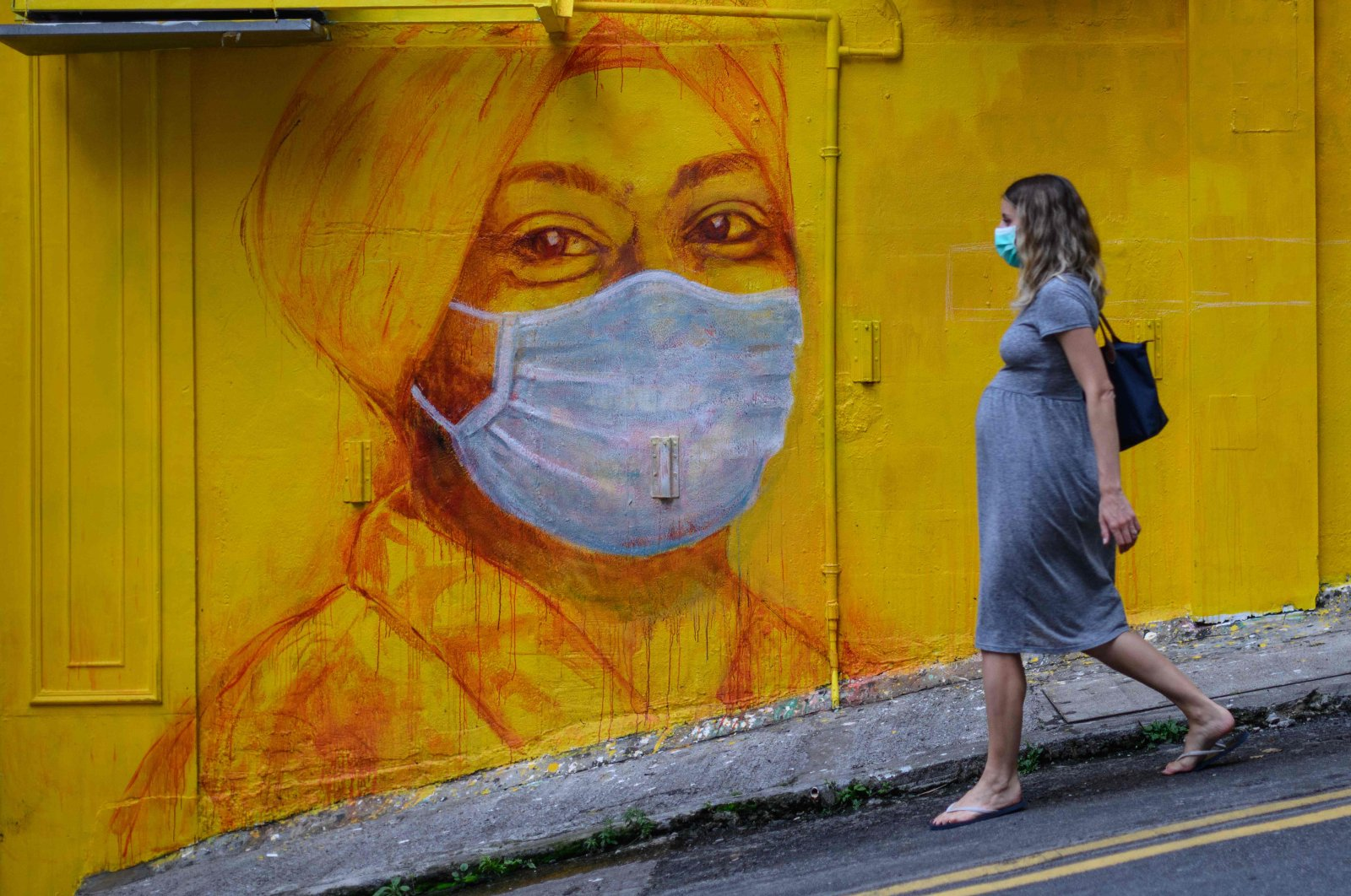 A pregnant woman wearing a face mask walks past a street mural in Hong Kong, March 23, 2020.