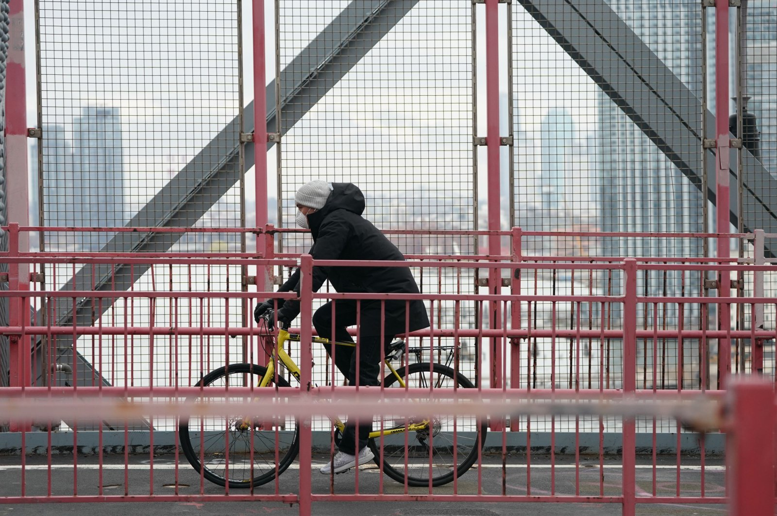 A cyclist wearing a mask rides over the Williamsburg Bridge in the Borough of Brooklyn on March 25, 2020 in New York. (AFP Photo)
