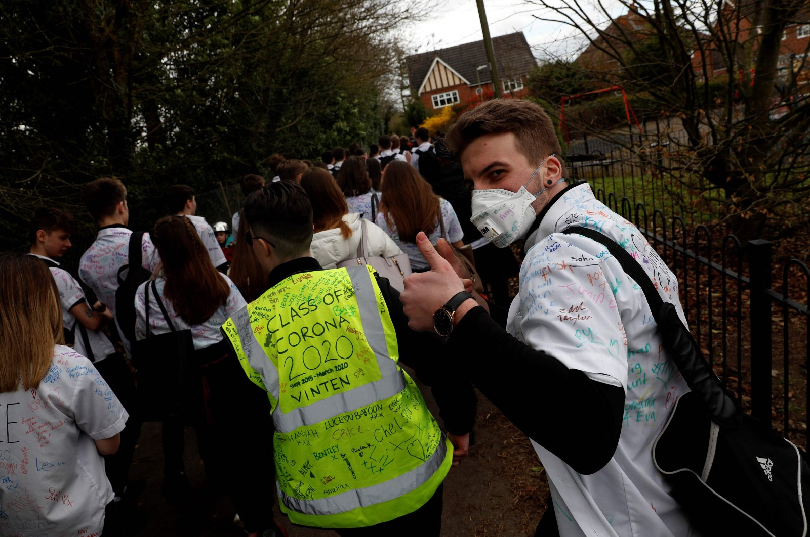 Year 11 pupils, some with graffiti-covered shirts reading 'Survivor 2020' and 'Class of Corona 2020' react as they leave a secondary school in Odiham, west of London on March 20, 2020.