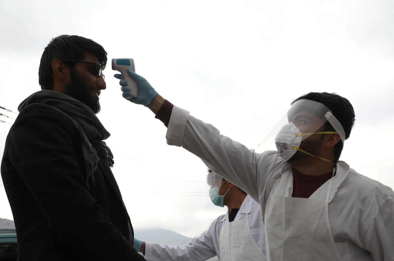 A medical official in protective gear checks the body temperature of a traveller, who arrives from provinces, amid concerns about the spread of coronavirus disease (COVID-19), in Kabul, Afghanistan March 24, 2020. (Reuters Photo)