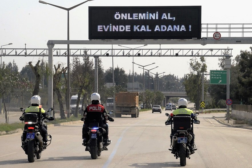 Policemen riding their motorcycles pass under a sign reading,