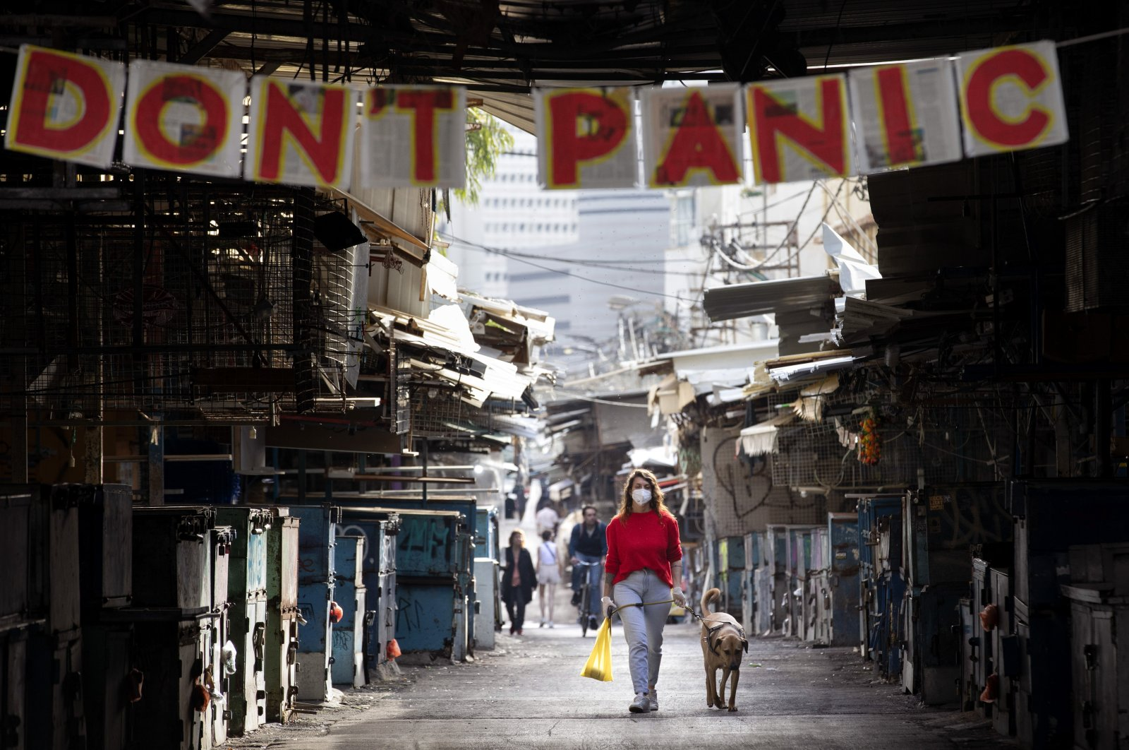 """A woman walks her dog under a """"don't panic"""" sign hanging across the entrance of a food market that was shut down in order to reduce the spread of the coronavirus, in Tel Aviv, Israel, Monday, March 23, 2020. (AP Photo)"""