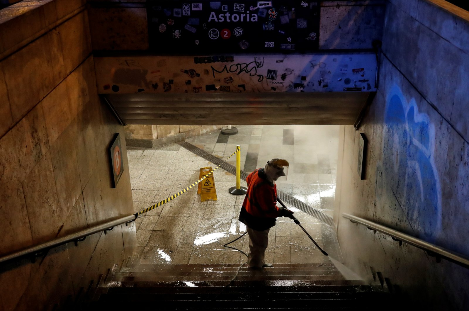 A worker cleans a flight of stairs of an underpass, amid the COVID-19 outbreak, in downtown Budapest, Hungary, Wednesday, March 25, 2020. (Reuters Photo)