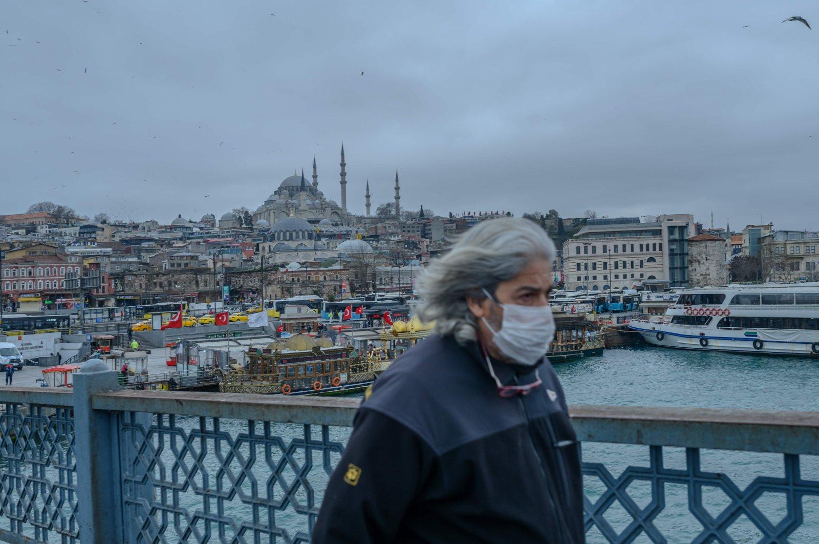 A man walks across Galata Bridge in central Istanbul, deserted due to the novel coronavirus outbreak, Thursday, March 26, 2020. (AFP Photo)