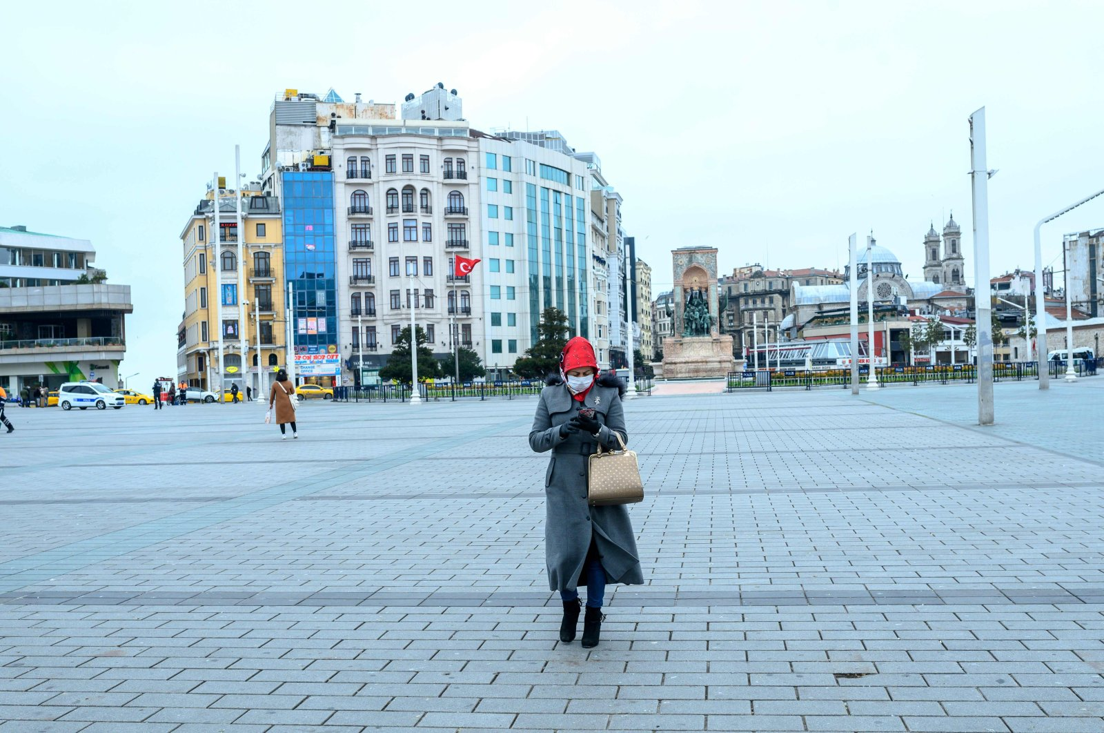 A woman wearing a mask walks across Taksim Square, Istanbul, Turkey, Thursday, March 26, 2020. (AFP Photo)