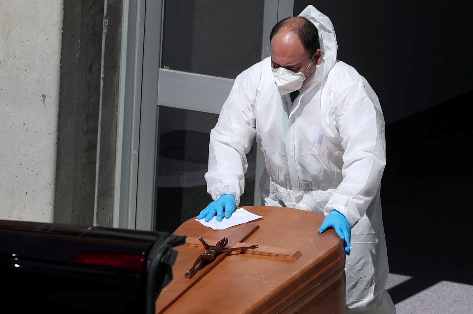 A funeral worker wearing a protective suit carries a coffin out of the morgue at Severo Ochoa Hospital, during the COVID-19 outbreak in Leganes, Spain, Thursday, March 26, 2020. (Reuters Photo)