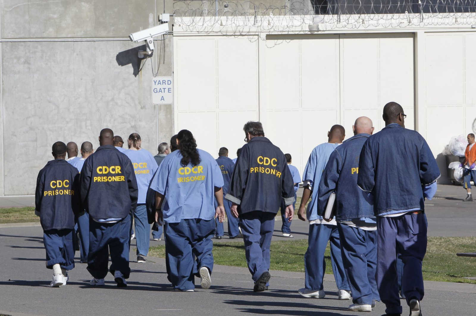 Inmates walk through the exercise yard at California State Prison, Sacramento, Calif., Thursday, Feb. 26, 2013. (AP Photo)