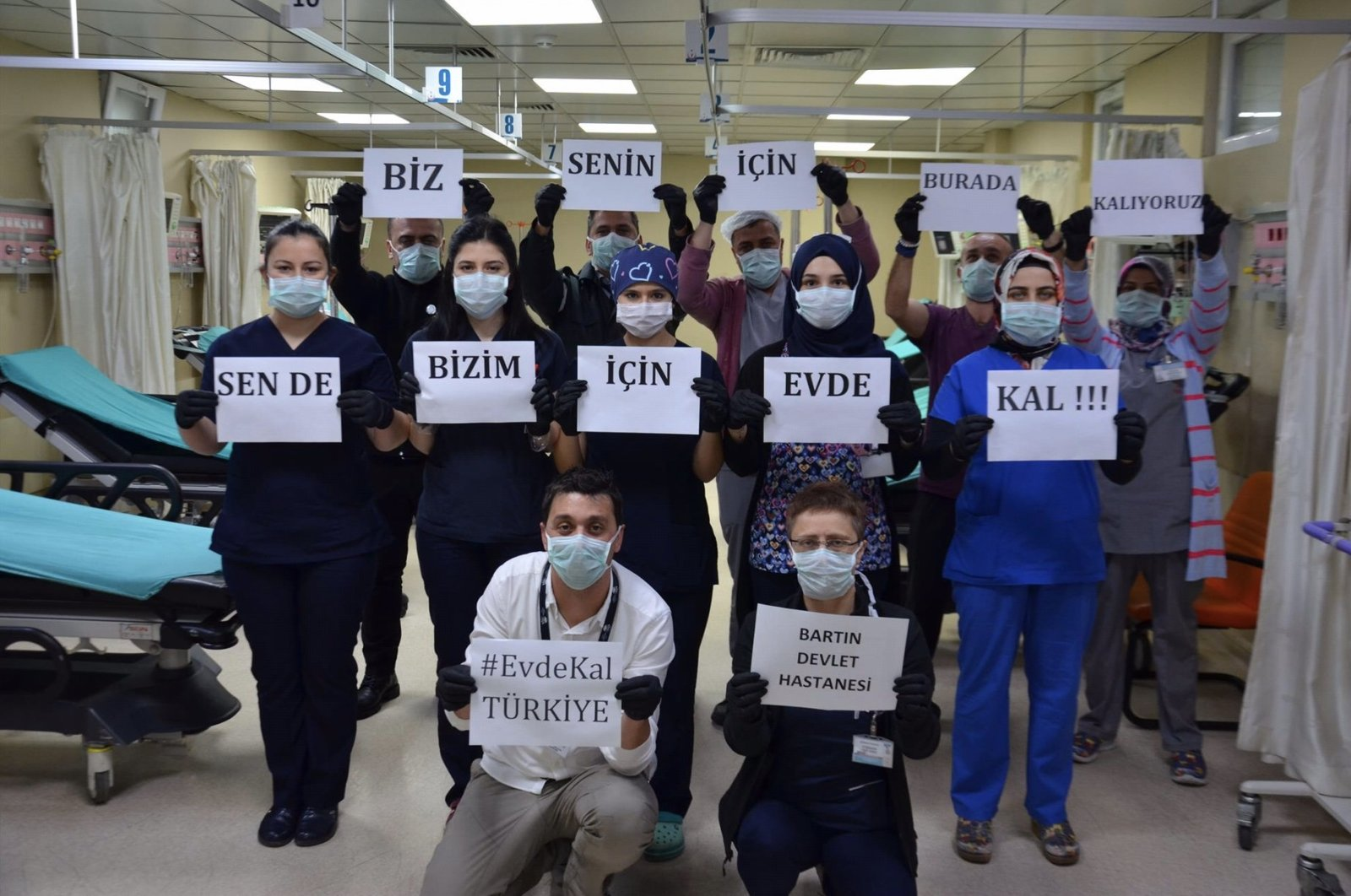 "Hospital staff in Bartın, Turkey, hold signs that read ""We stay here for you, you stay home for us,"" Friday, March 20, 2020. (AA Photo)"